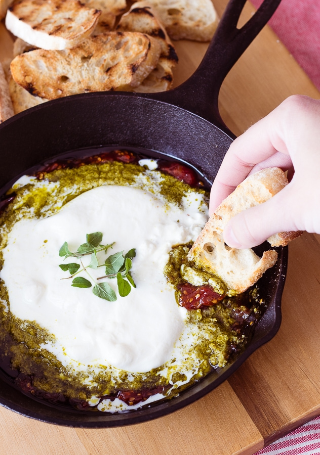 burrata cheese tomato jam and pesto in a cast iron skillet with toasted bread