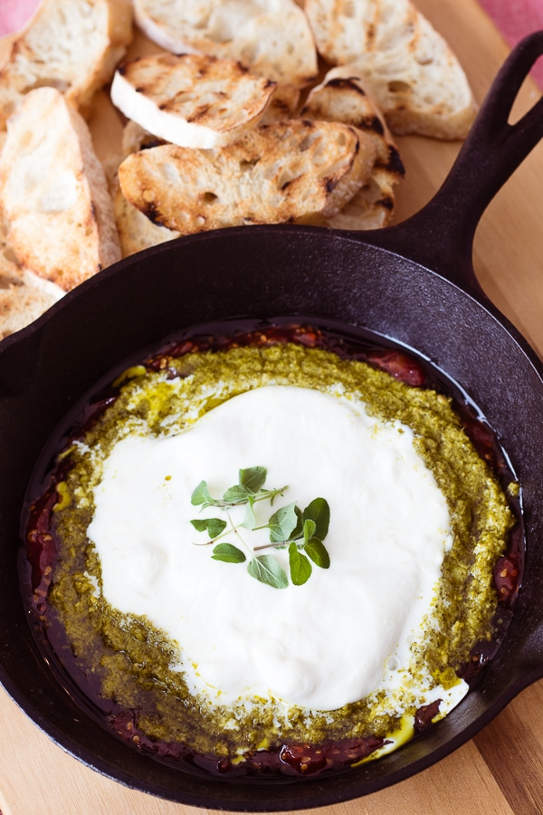 Burrata Tomato Jam and Pesto dip in a cast iron skillet with toasted crostini