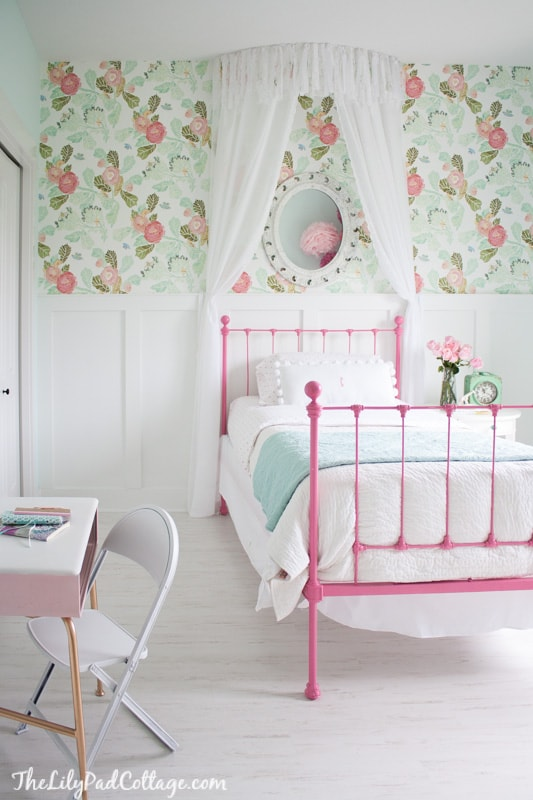 little girl wallpapered bedroom