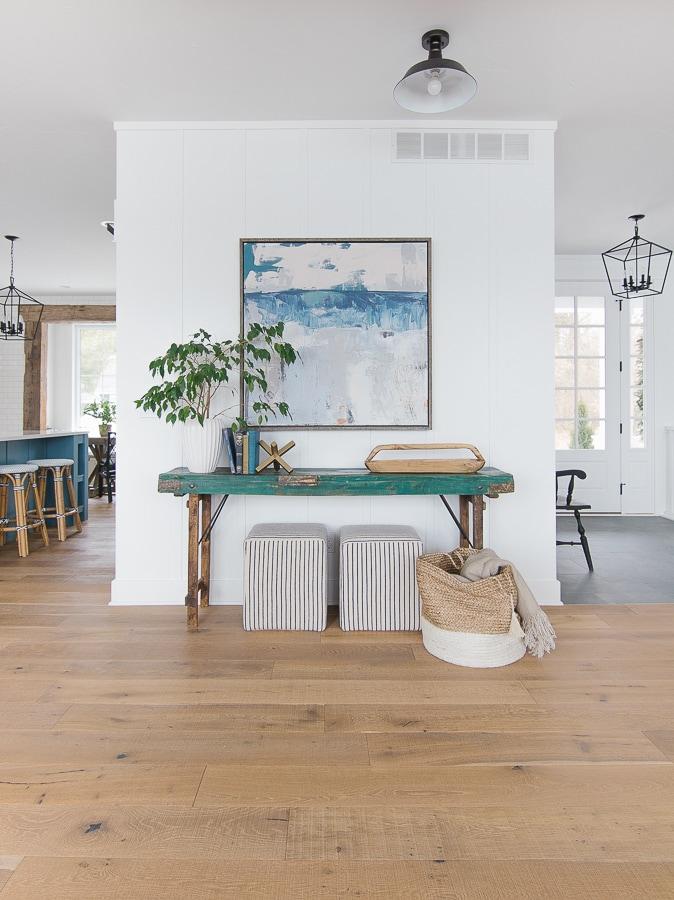 green table, coastal wall art, striped ottomans