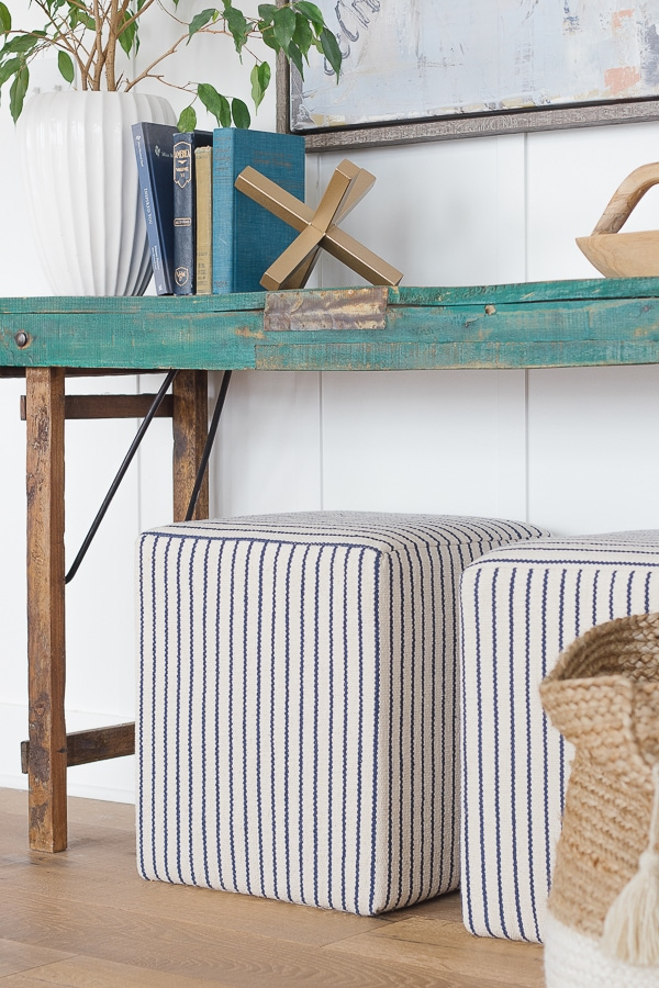 striped ottomans under green console table