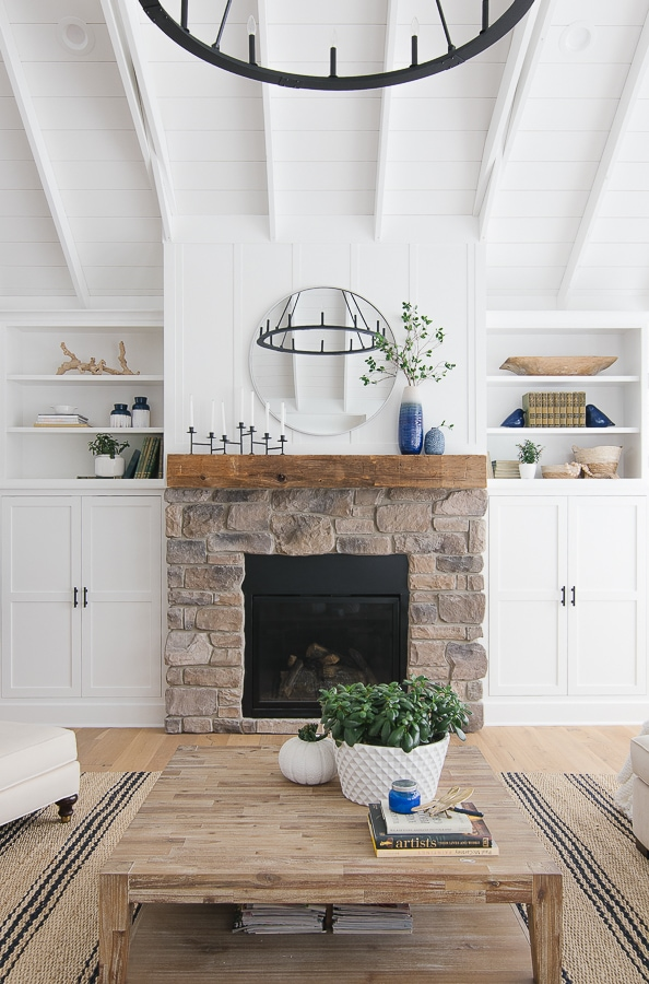 lake house bookshelf styling. Rustic stone mantel and white shelving.