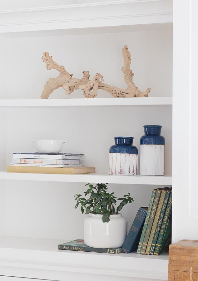 lake house bookshelf styling. Rustic stone mantel and white shelving.