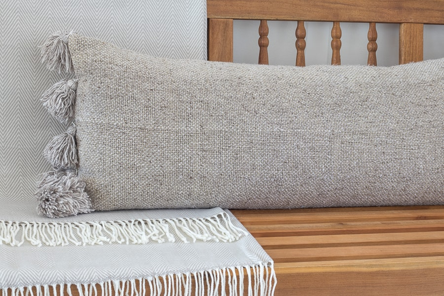 light wood bench neutral blanket and pillow
