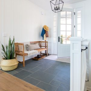 lake house entryway slate floors white board and batten and light wood entry bench
