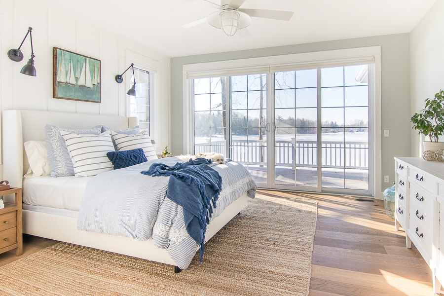 white upholstered bed with blue bedding in a lake house master bedroom