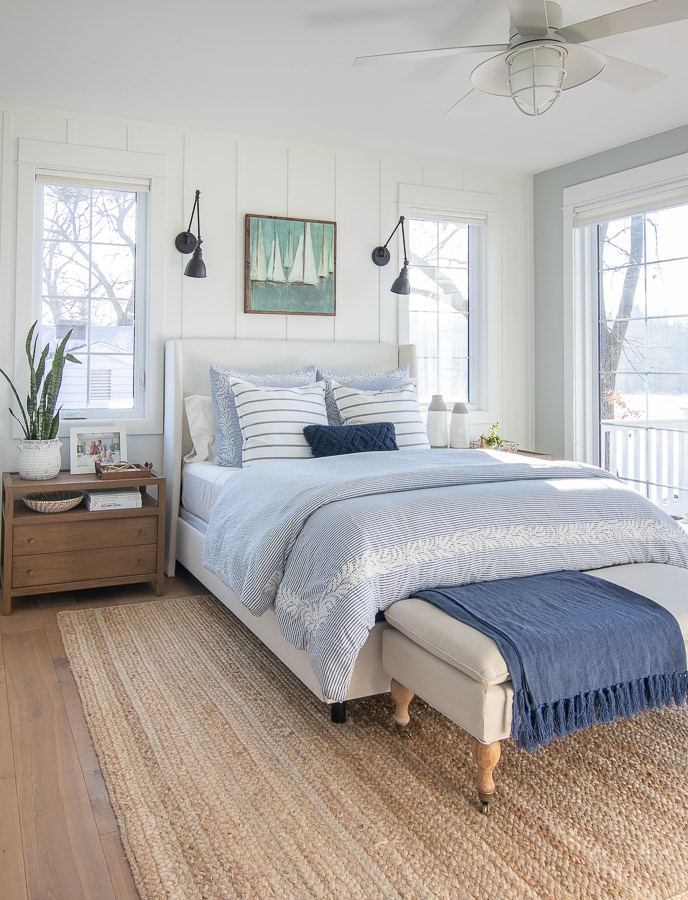 lake house master bedroom white upholstered bed blue bedding jute rug
