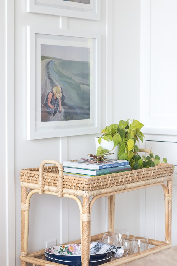 Lake house dining space, rattan bar cart, coastal art