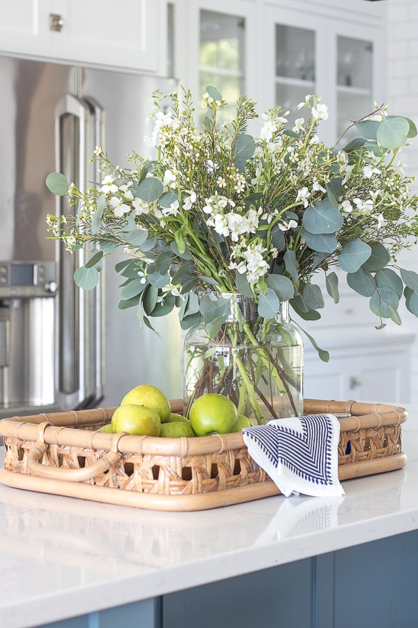 kitchen island cane tray vase of flowers green apples