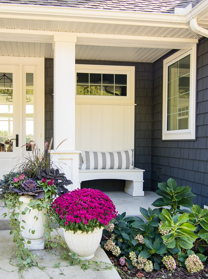 Striped gray pillows and purple mums with gray exterior house fall front porch