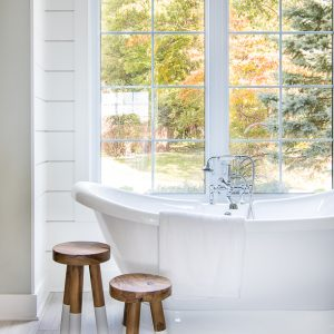 white and blue coastal master bathroom free standing tub and wood stools