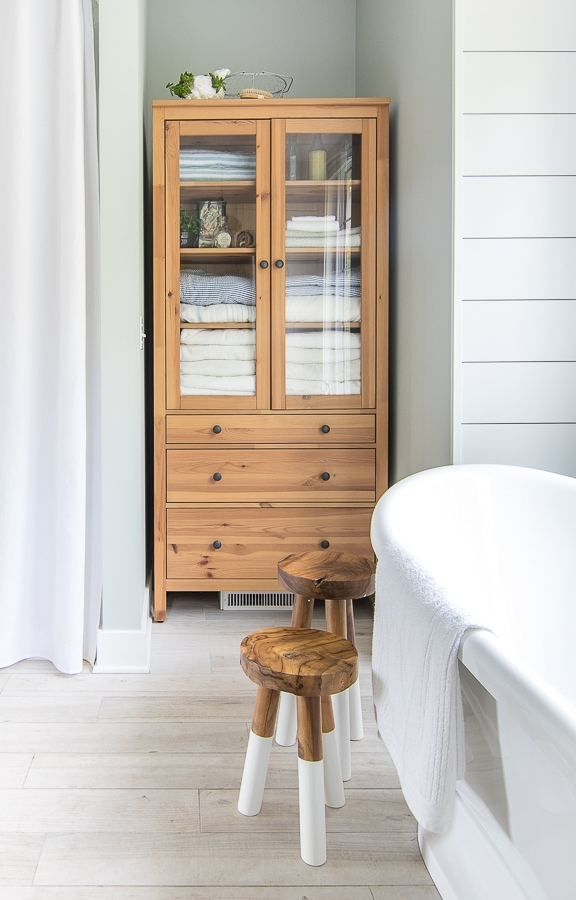 wood and glass linen cabinet coastal lake house master bathroom