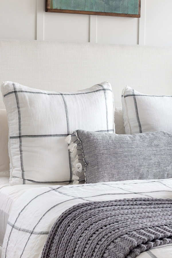 cozy winter master bedroom lake house. White and gray bedding and walls