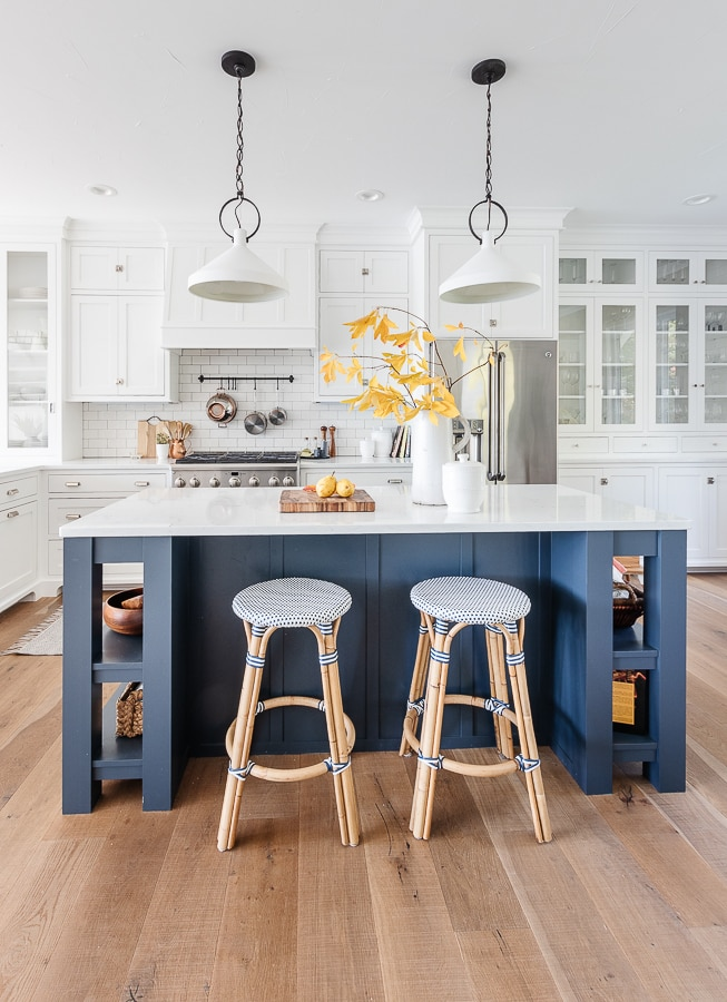 white pendants, navy island, white cabinets lake house kitchen
