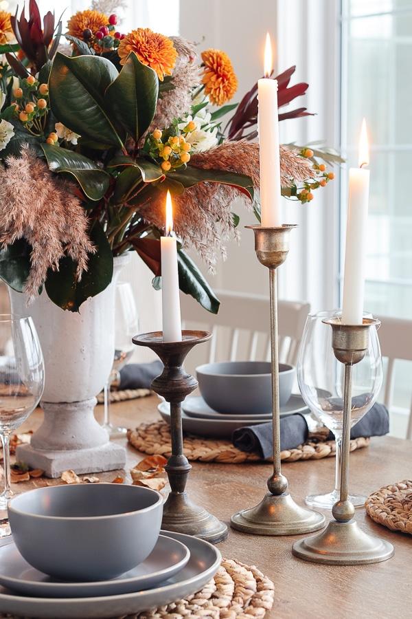 brass candlesticks rattan place mats, gray dishes