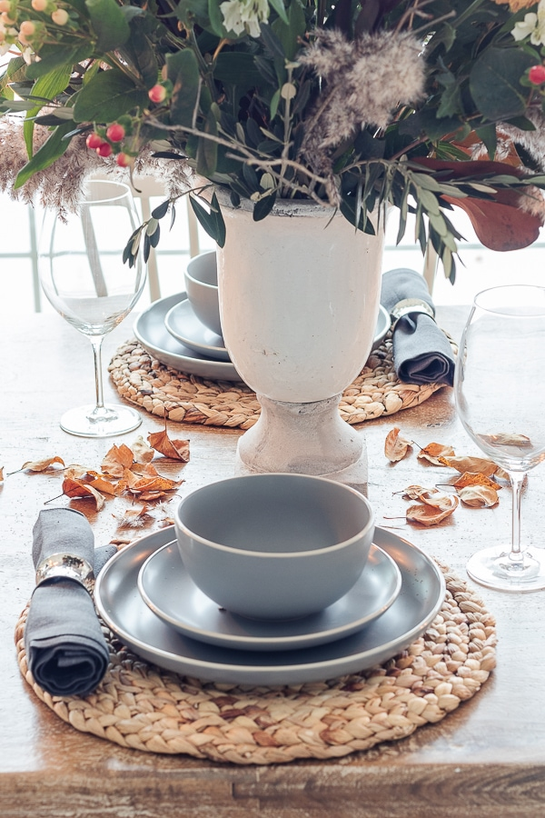 gray dishes, warm fall colored flowers, and rattan place mats