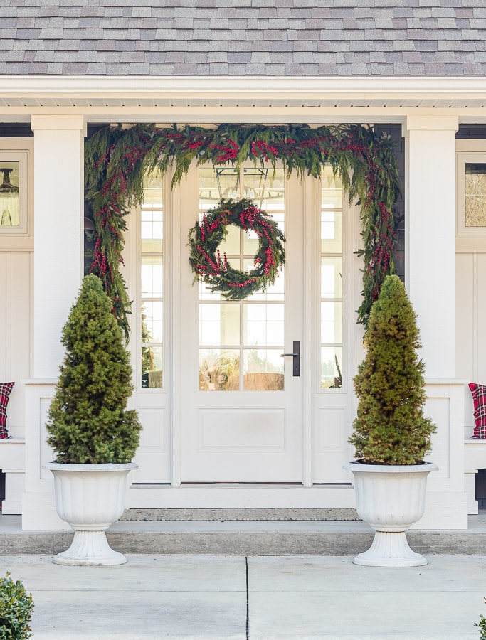 Dark grey home with decorated front porch with red and green Christmas decor.