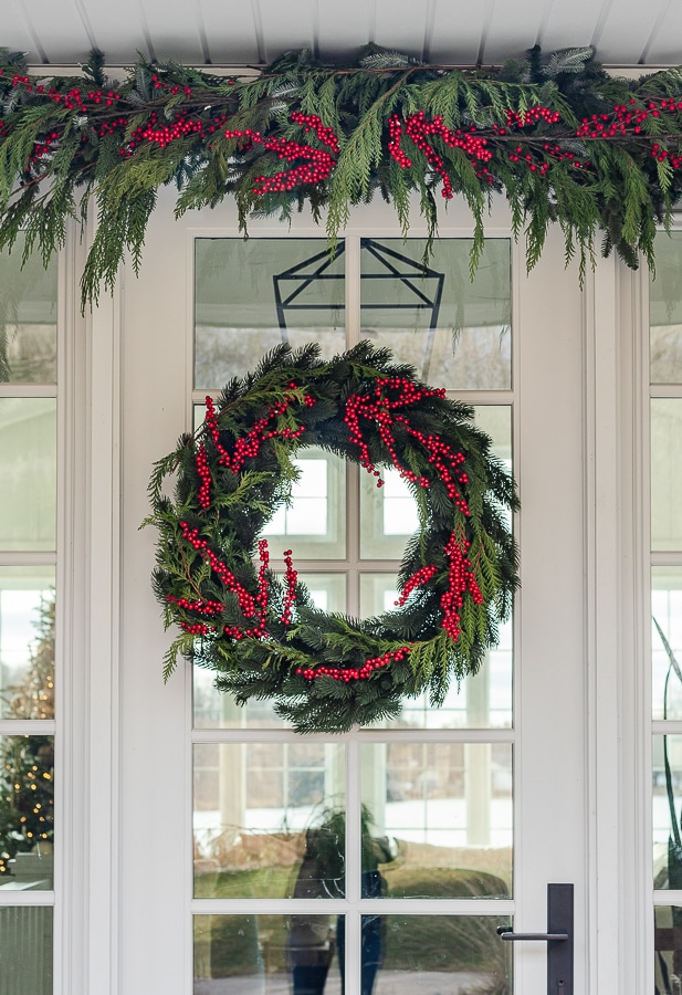 Cedar wreath with red berries on white front door.
