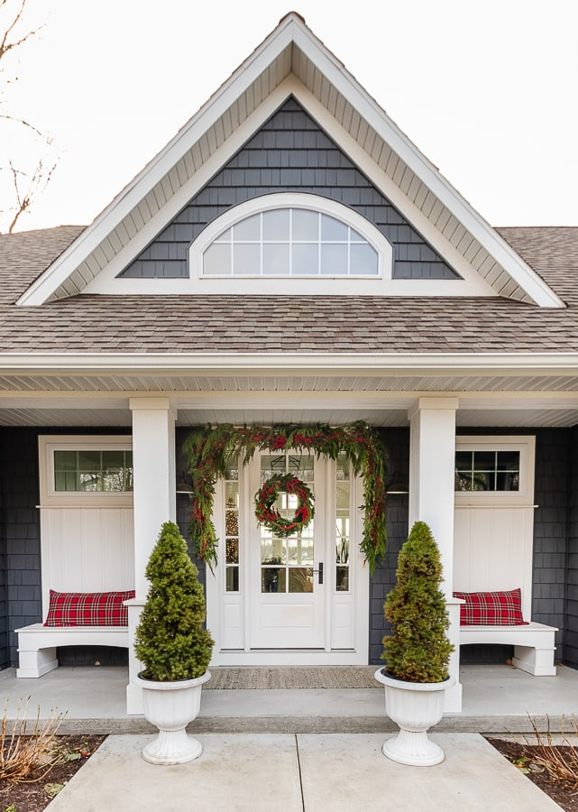 House decorated for Christmas front porch with red plaid pillows and cedar garland