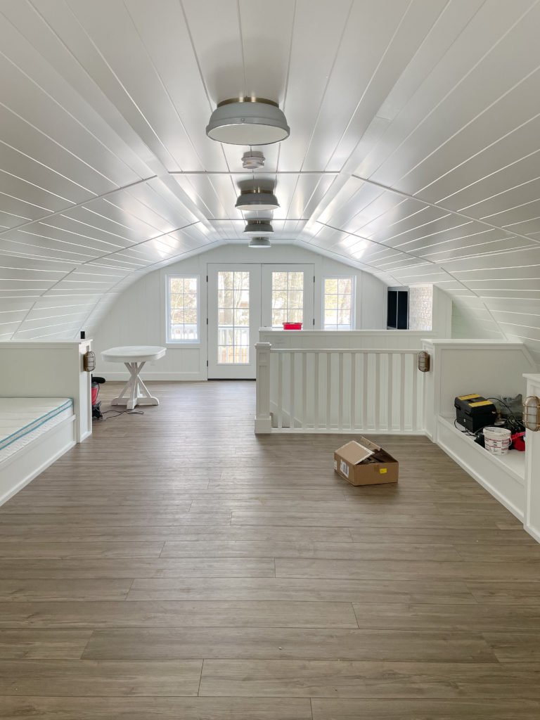 bunk room with white walls and wood floors