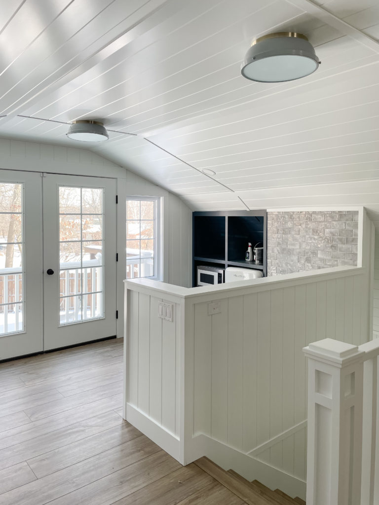 white planked walls and luxury vinyl plank flooring mini kitchen pool house