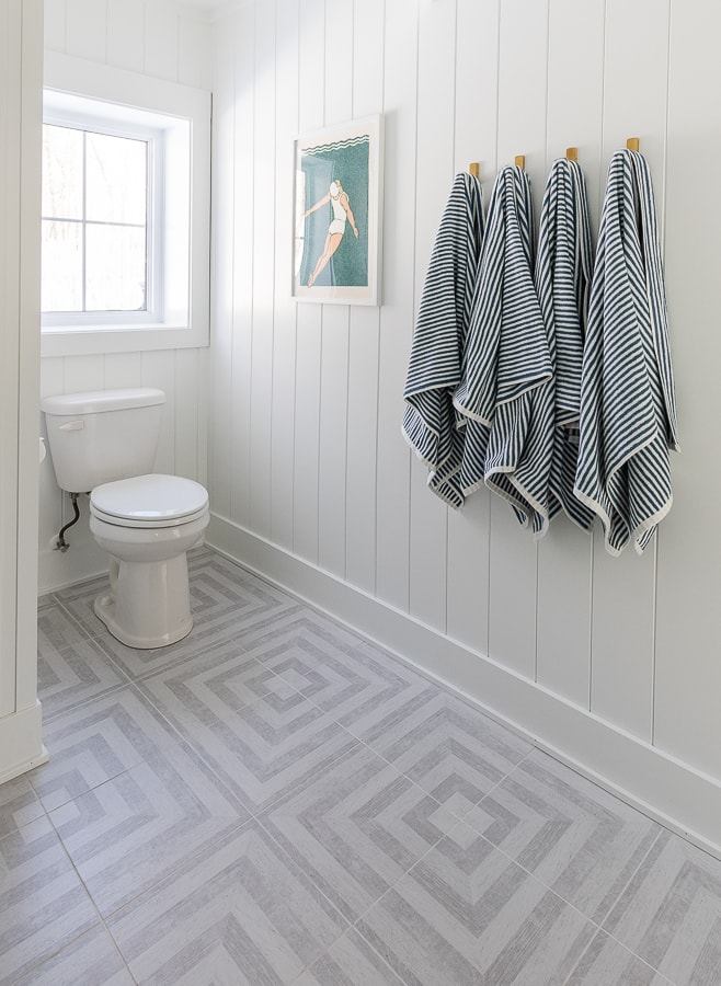 blue and white striped towels, gray patterned floors, white paneled walls bathroom