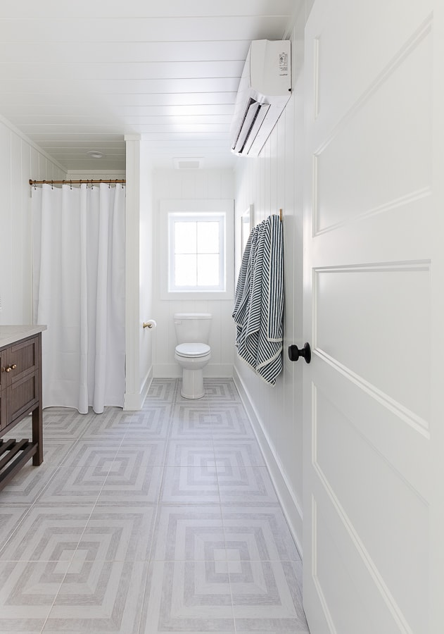 gray patterned floor, white paneled walls bathroom