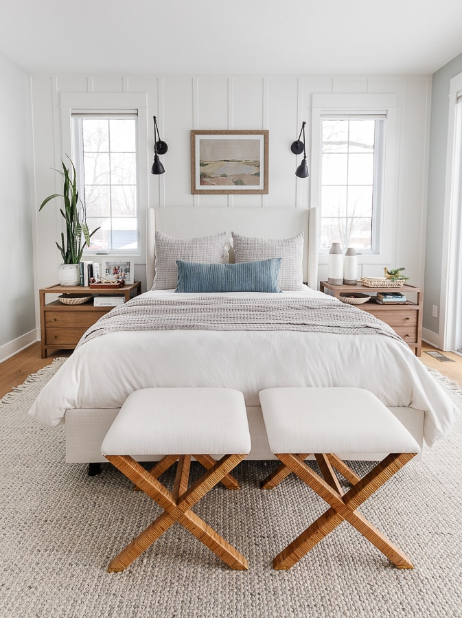 white walls, coastal wall art. white bed with windows on either side. Blue and gray bedding. Coastal bedroom design