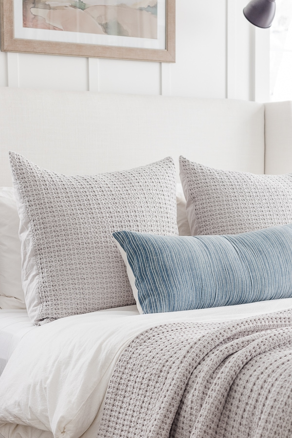 waffle knit euro shams and throw blanket in gray with blue accent throw pillow. Lake house bedroom.