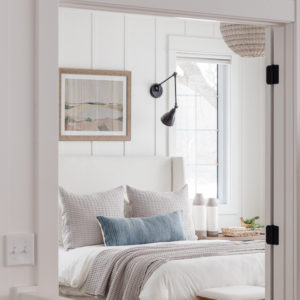 white walls white bedding gray and blue bedding in bedroom