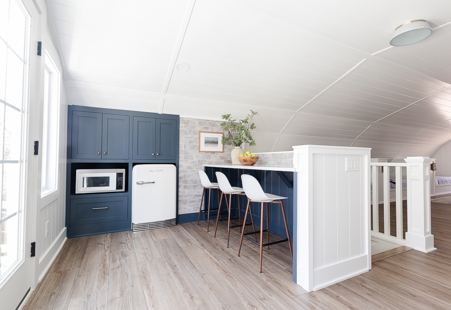 white wall room with navy cabinets and gray tile snack bar