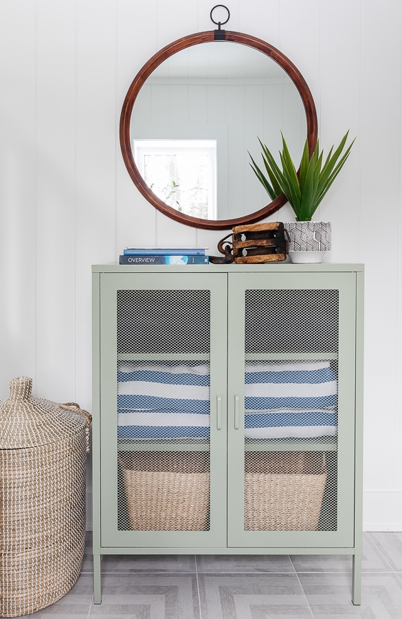 green metal cabinet, grey and white patterned tile flooring white paneled walls pool house mudroom