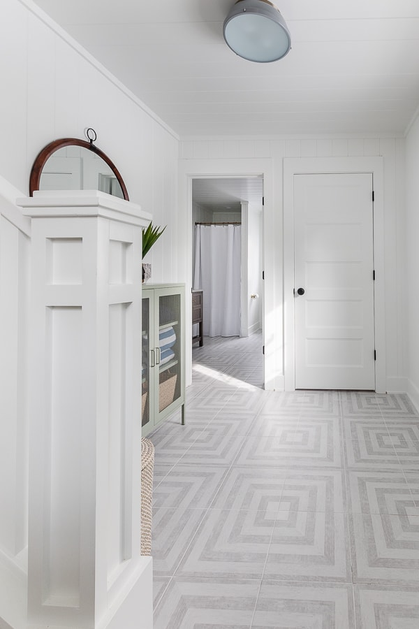 Gray and white patterned tile, white paneled walls, green cabinet