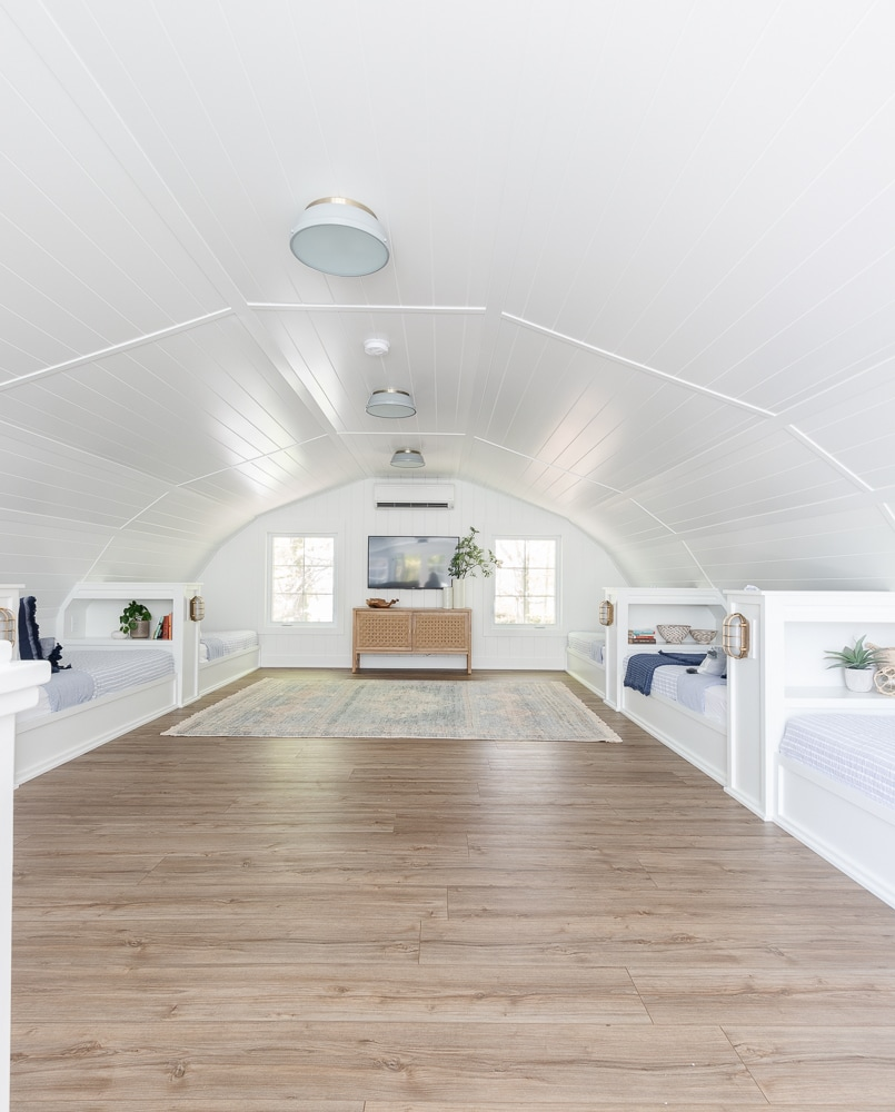 white planked lake house bunk room with blue and white bedding and warm wood floors