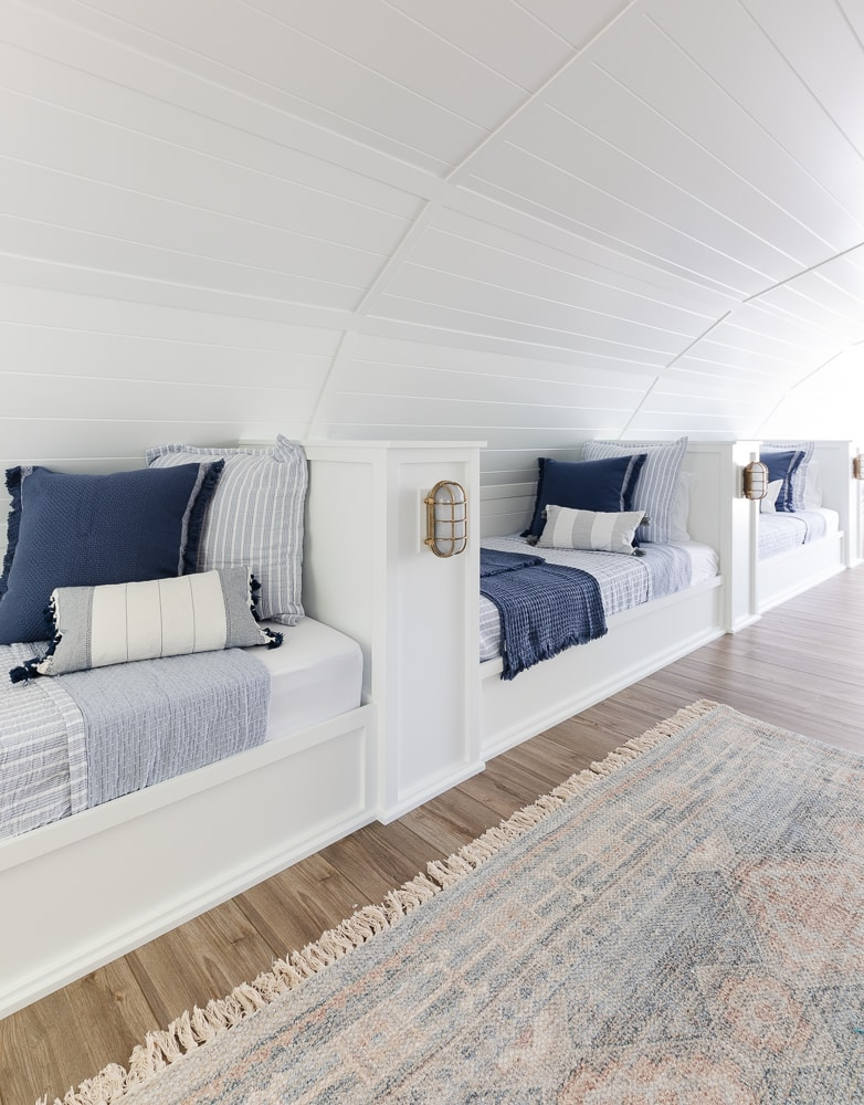built in beds in a lake house bunk room with blue and white bedding and throw pillows
