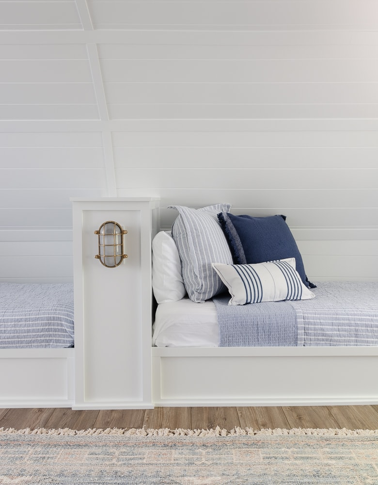lake house bunk room with blue and white bedding and throw pillows