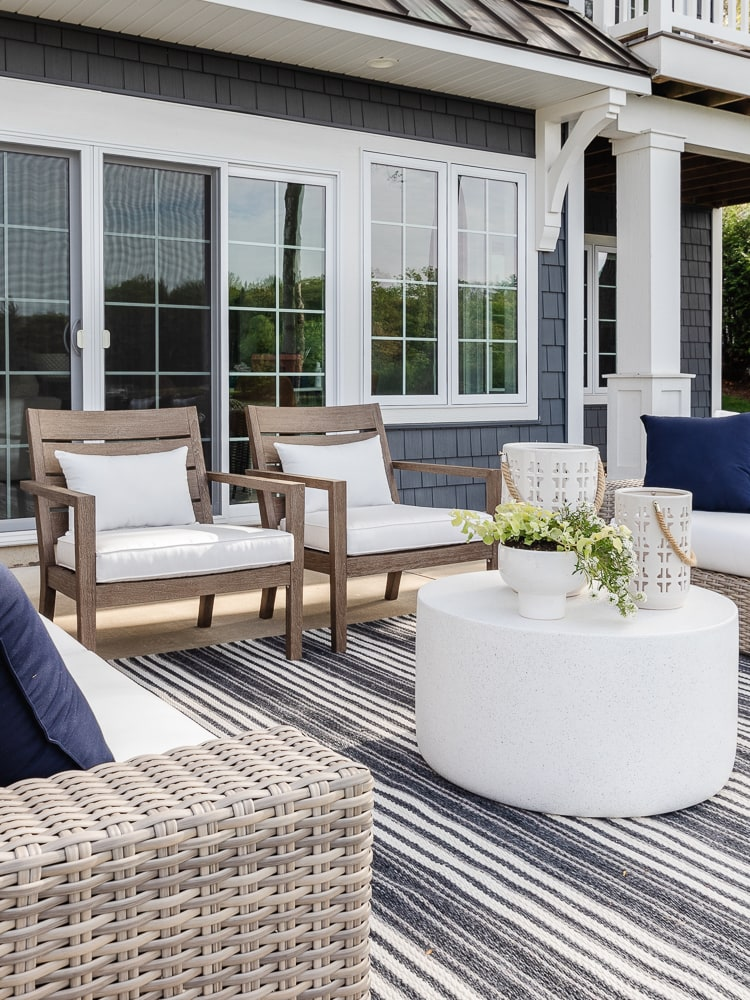 grey outdoor wicker sofa, striped rug, cement coffee table white planters
