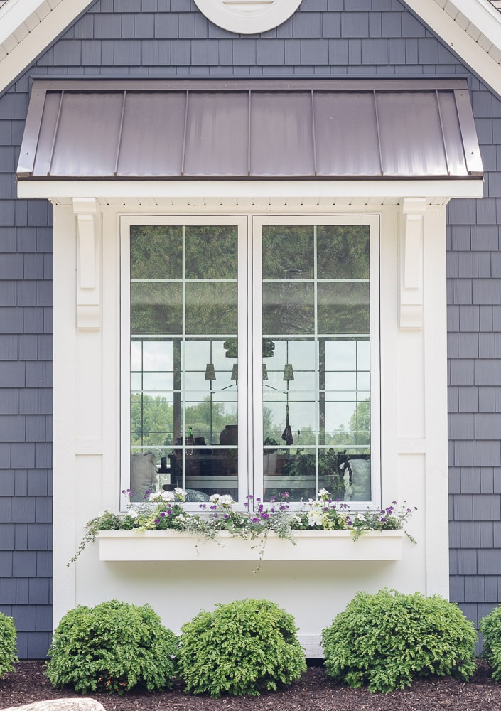 white and gray house with white window boxes