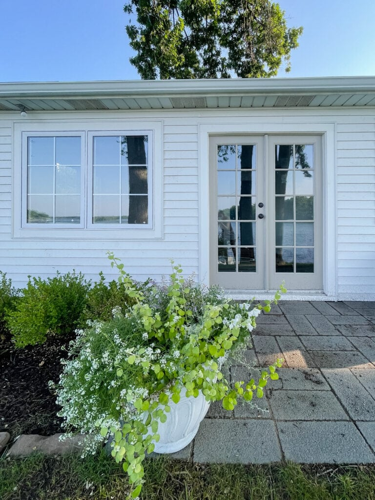 white lake house guest cottage with gray french doors