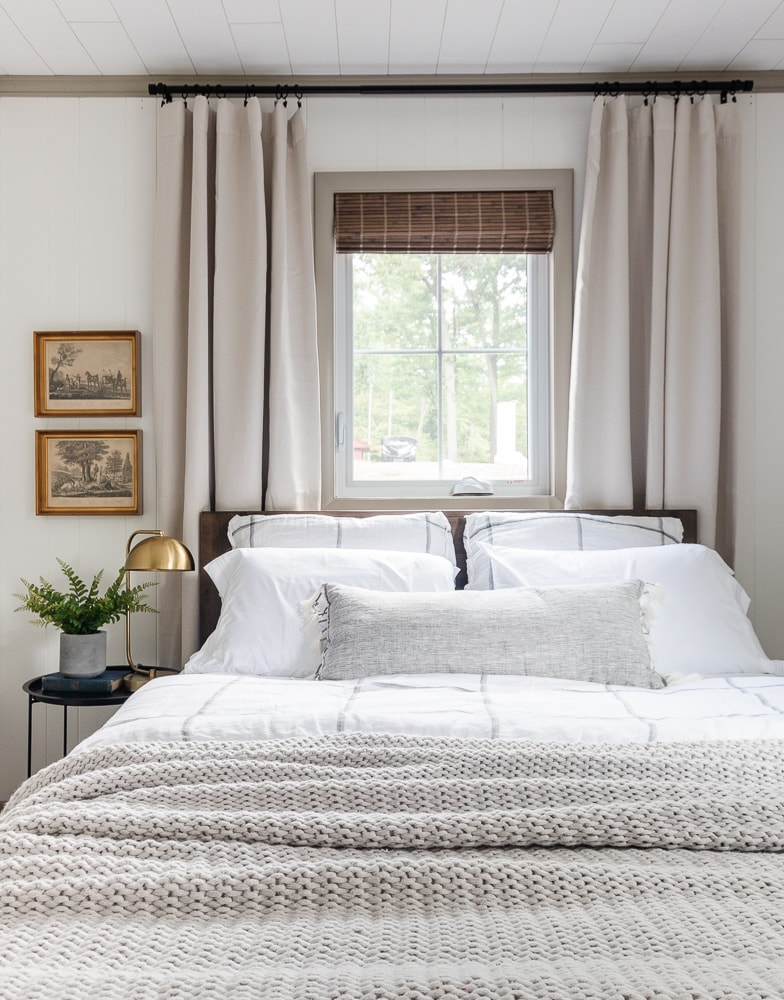 bedroom with white walls, gray and white window pane bedding gray drapes and bamboo shades