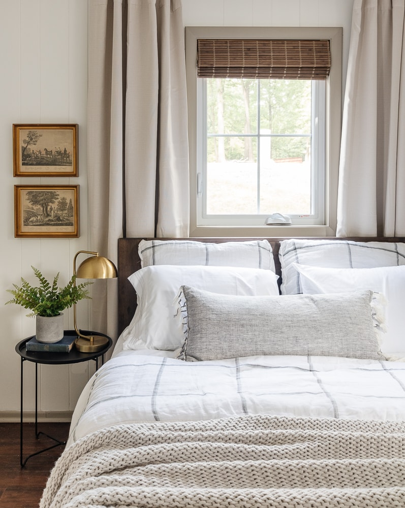 gray and white bedroom with gray drapes, bamboo shades and white walls
