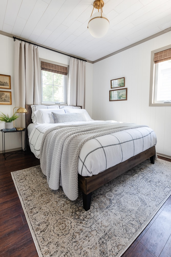 guest bedroom with gray and white bedding, white walls, gray trim, gray drapes and black and brass accents