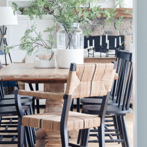 white lake house dining room with wood table and black and woven dining chairs